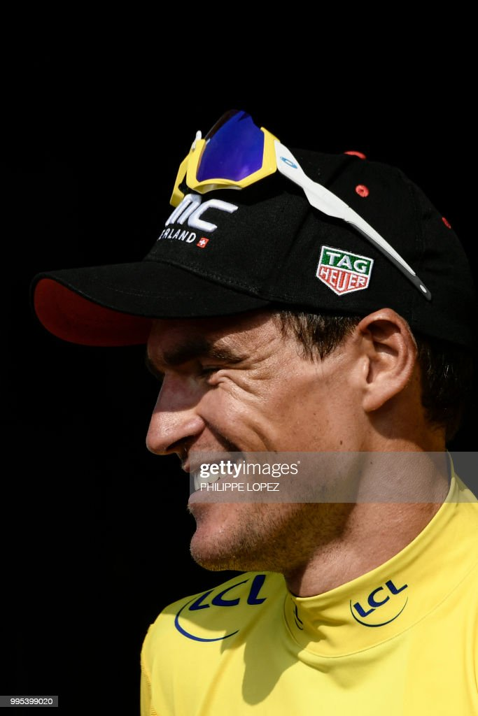 Belgium's Greg Van Avermaet, wearing the overall leader's yellow jersey, celebrates on the podium after the fourth stage of the 105th edition of the Tour de France cycling race between La Baule and Sarzeau, western France, on July 10, 2018.