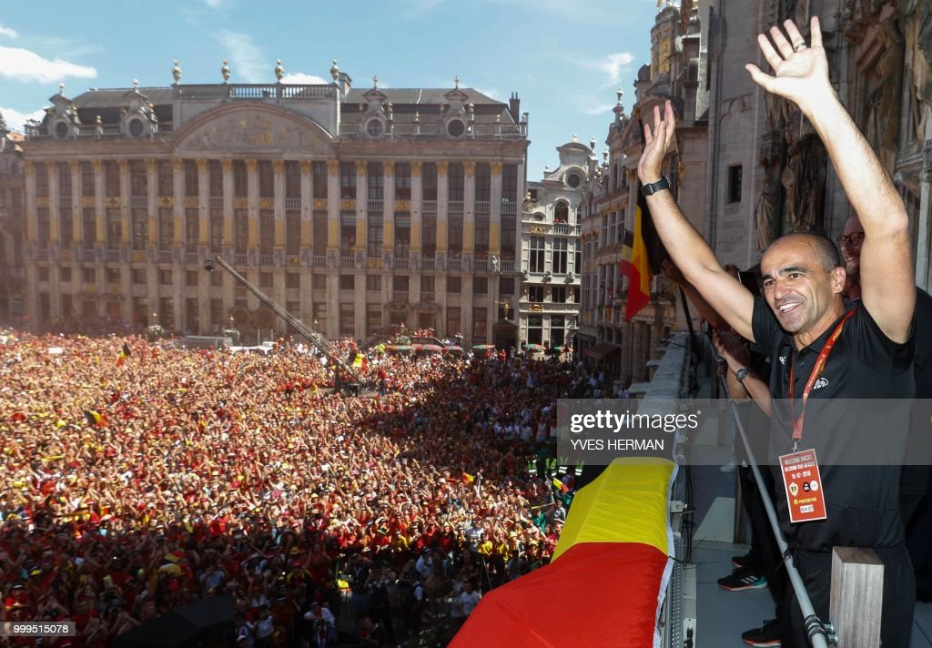 TOPSHOT - Belgium's head coach Roberto Martinez celebrates at the balcony in front of more than 8000 supporters at the Grand-Place, Grote Markt in Brussels city center, as Belgian national football team Red Devils arrive to celebrate with supporters at the balcony of the city hall after reaching the semi-finals and winning the bronze medal at the Russia 2018 World Cup, on July 15, 2018. (Photo by Yves HERMAN / BELGA / AFP) / Belgium OUT