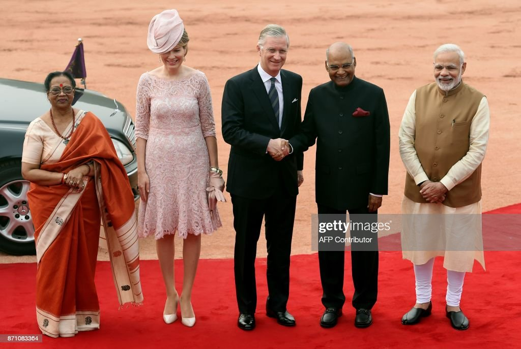 Belgium's King Philippe (L), accompanied by Queen Mathilde (2nd L), shakes hands with Indian President Ram Nath Kovind (2nd R) while accompanied by his wife Savita Kovind (L), as Indian Prime Minister Narendra Modi (R) looks on during a ceremonial reception at the Indian Presidential palace in New Delhi on November 7, 2017. Belgium's King Philippe and Queen Mathilde are on a state visit to India until November 11. SHARMA