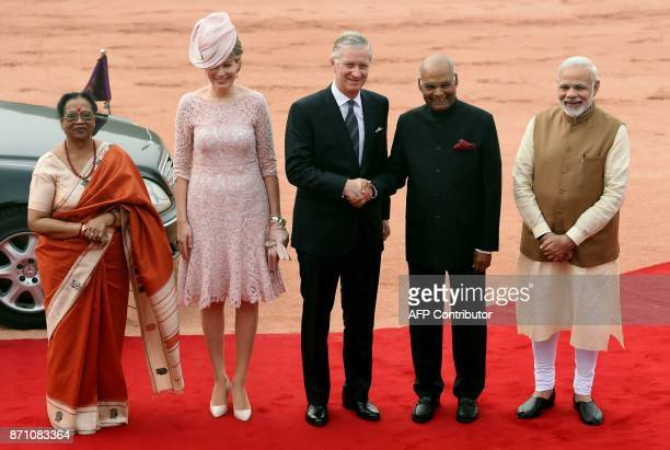 Belgium's King Philippe accompanied by Queen Mathilde shakes hands with Indian President Ram Nath Kovind while accompanied by his wife Savita Kovind...