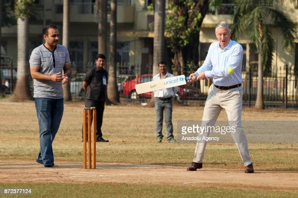 Belgium's King Philippe hits a ball as he plays cricket with children at a ground in Mumbai India November 10 2017