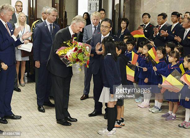 Belgium's King Philippe receives flowers from children as he visits the Aichi Prefectural government building in Nagoya central Japan on Oct 13 2016...