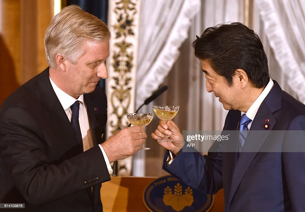 Belgium's King Philippe (L) toasts Japan's Prime Minister Shinzo Abe (R) at the opening of a dinner at state guest house in Tokyo on October 12, 2016. The Belgian royal couple are on a six-day state visit to Japan that began on October 10. / AFP / POOL / Kazuhiro NOGI