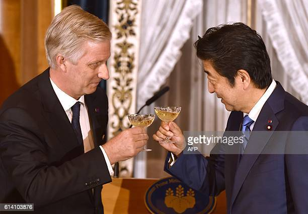Belgium's King Philippe toasts Japan's Prime Minister Shinzo Abe at the opening of a dinner at state guest house in Tokyo on October 12 2016 The...