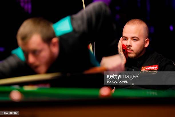 Belgium's Luca Brecel looks on as Northern Ireland's Mark Allen plays a shot during their firstround match in the Masters snooker tournament at...