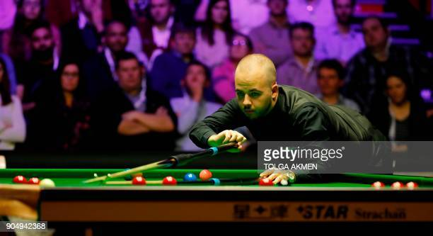 Belgium's Luca Brecel plays a shot against Northern Ireland's Mark Allen during their firstround match in the Masters snooker tournament at Alexandra...