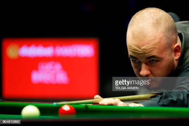 Belgium's Luca Brecel plays a shot during his firstround match against Northern Ireland's Mark Allen in the Masters snooker tournament at Alexandra...