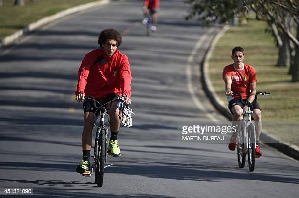 Belgium's midfielder Axel Witsel and teammate Adnan Januzaj ride bicycles as they arrive for a training session in Mogi das Cruzes on June 27 during...