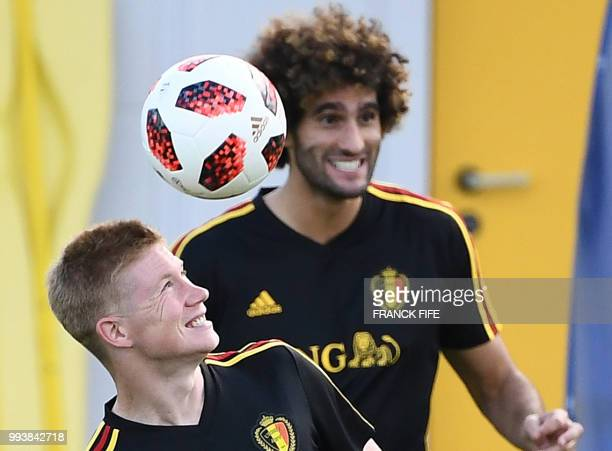 Belgium's midfielder Kevin De Bruyne heads the ball next to Belgium's midfielder Marouane Fellaini during training session of Belgium's national...