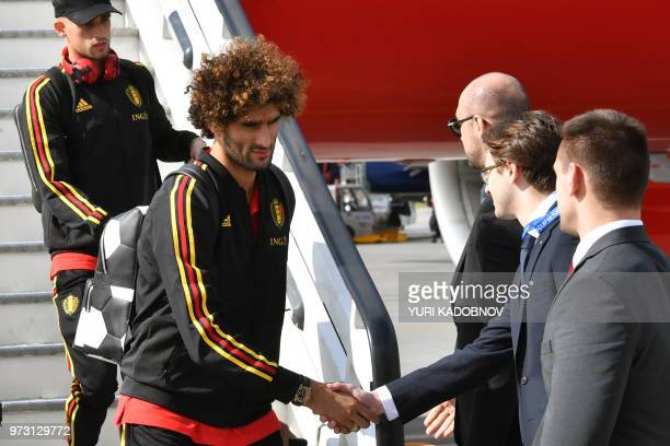 Belgium's midfielder Marouane Fellaini is welcomed by officials upon the team's arrival at Moscow's Sheremetyevo airport on June 13 ahead of the...