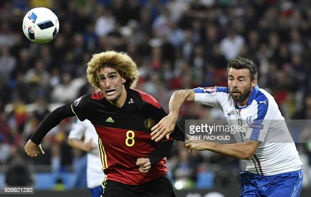 TOPSHOT Belgium's midfielder Marouane Fellaini vies for the ball against Italy's defender Andrea Barzagli during the Euro 2016 group E football match...