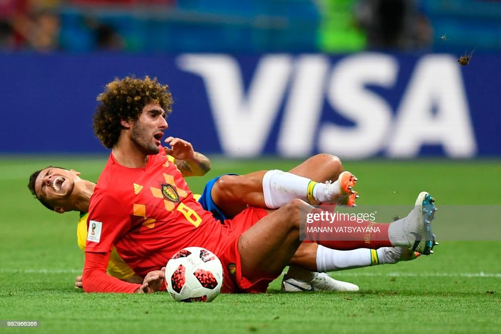 TOPSHOT - Belgium's midfielder Marouane Fellaini (C) vies for the ball with Brazil's forward Philippe Coutinho (background) during the Russia 2018 World Cup quarter-final football match between Brazil and Belgium at the Kazan Arena in Kazan on July 6, 2018. (Photo by Manan VATSYAYANA / AFP) / RESTRICTED