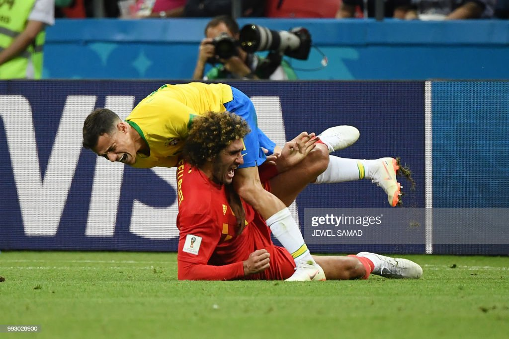 TOPSHOT - Belgium's midfielder Marouane Fellaini (bottom) vies for the ball with Brazil's forward Philippe Coutinho during the Russia 2018 World Cup quarter-final football match between Brazil and Belgium at the Kazan Arena in Kazan on July 6, 2018. (Photo by Jewel SAMAD / AFP) / RESTRICTED