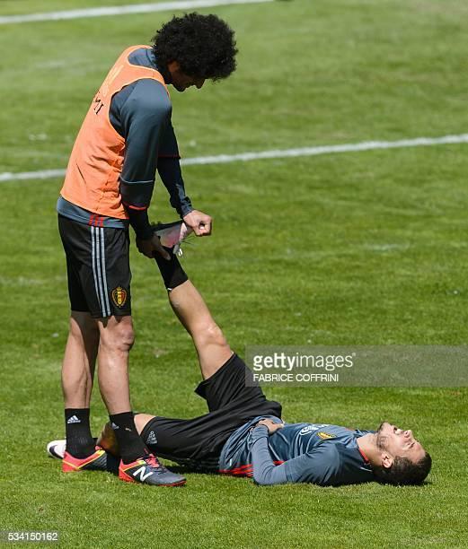 Belgium's national football team midfielder Marouane Fellaini helps teammate midfielder Eden Hazard during a training at the JuanAntonioSamaranch on...