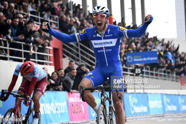 Belgium's Philippe Gilbert celebrates his victory as he crosses the finish line past Germany's Nils Politt competes during the 117th edition of the...