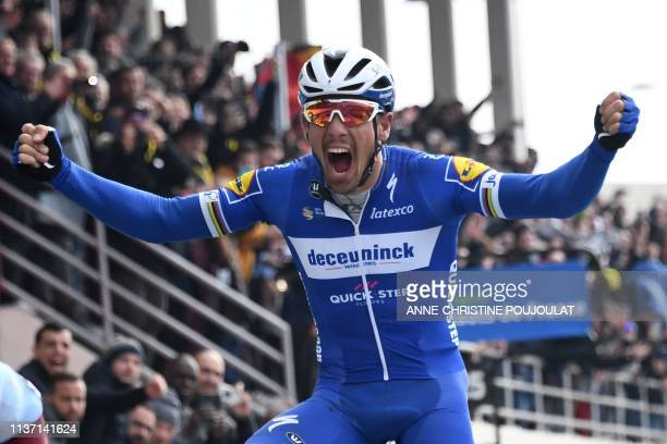 Belgium's Philippe Gilbert celebrates his victory as he crosses the finish line of the 117th edition of the Paris-Roubaix one-day classic cycling...