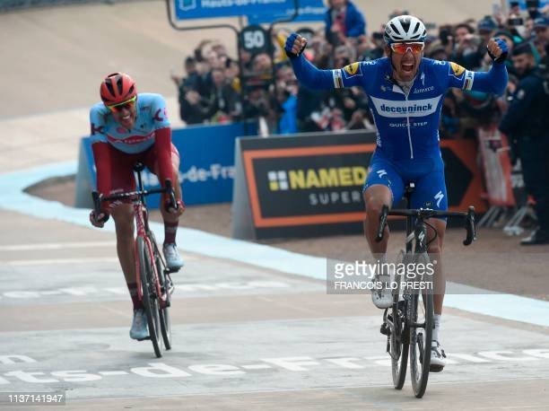 Belgium's Philippe Gilbert celebrates his victory as he crosses the finish line past Germany's Nils Politt during the 117th edition of the...
