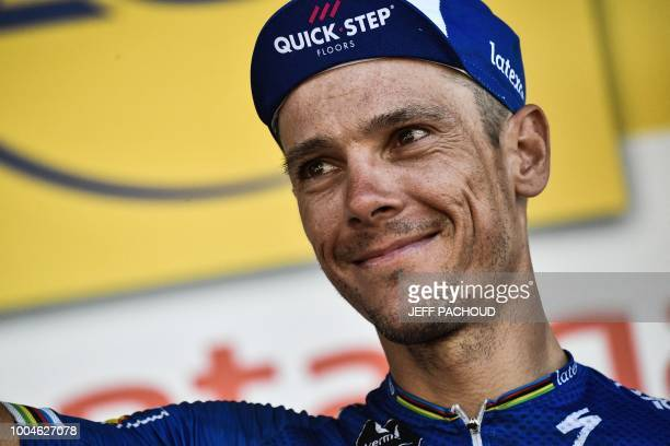Belgium's Philippe Gilbert celebrates on the podium after receiving a prize for being the stage's most aggressive rider, following the 16th stage of...