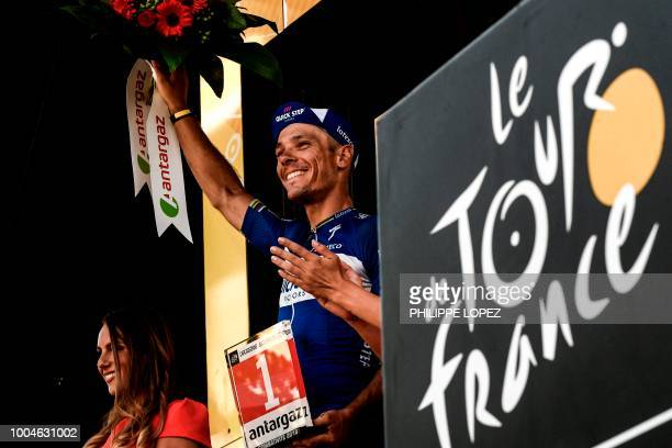 Belgium's Philippe Gilbert celebrates on the podium after receiving a prize for being the stage's most aggressive rider following the 16th stage of...