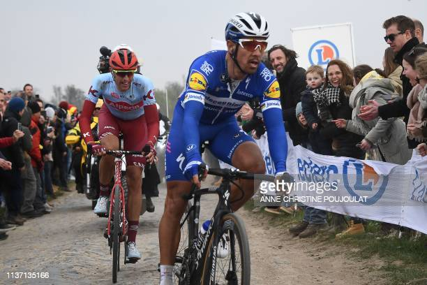 Belgium's Philippe Gilbert rides followed by Germany's Nils Politt on the Carrefour de l'Arbre cobbled stones sector during the 117th edition of the...