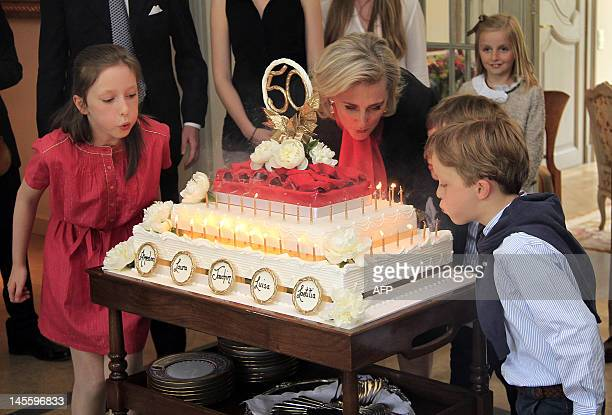 Belgium's Princess Laetitia Maria Princess Astrid and Prince Aymeric try to blow out the candles on a birthday cake during the celebrations for the...