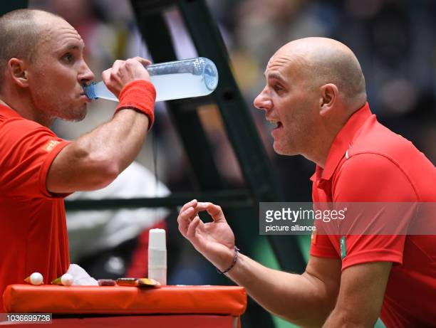 Belgium's team coach Johan Van Herck talks to Steve Darcis during the Davis Cup World Group match between Germany and Belgium at the Fraport Arena in...