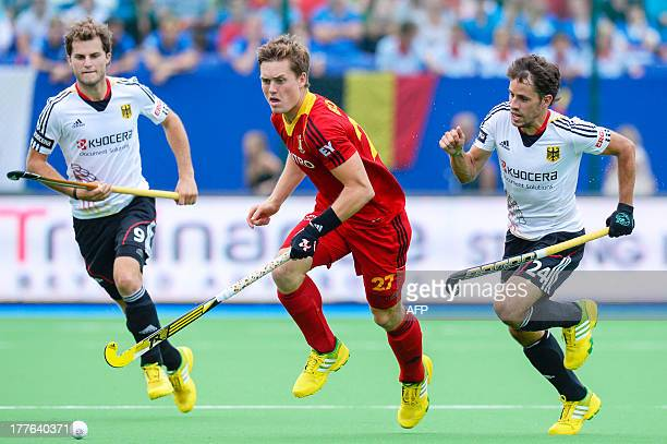 Belgium's Tom Boon and German Benedikt Furk run for the ball during the men's final fieldhockey match between Belgium and Germany at the 2013...