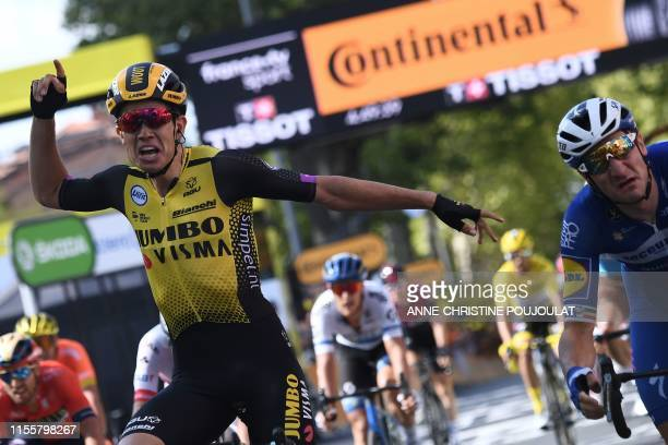 Belgium's Wout van Aert celebrates past Italy's Elia Viviani as he wins on the finish line of the tenth stage of the 106th edition of the Tour de...