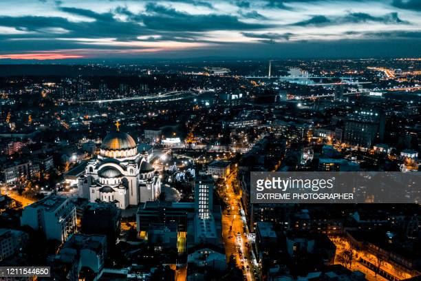 belgrade city lights and the illuminated st. sava temple, taken from a drone at golden hour - belgrade serbia stock pictures, royalty-free photos & images