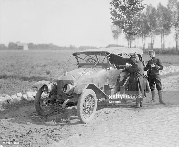 Belguim officers inspect a staff car which had been captured by the Germans along with its occupants. The Germans had donned the captured officers...