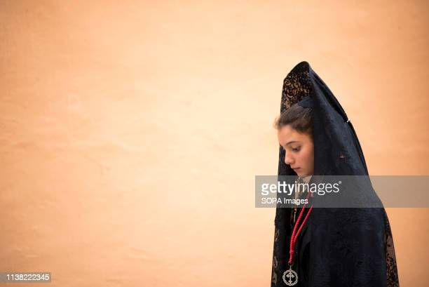 A believer dressed with mantilla seen taking part in the Good Friday procession in Granada Every year thousands of christians believers celebrates...