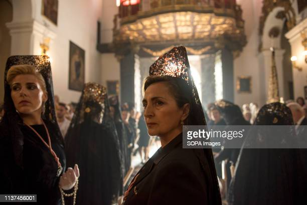 A believer from Los Dolores Brotherhood is seen looking back before taking part in the procession of the Holy Monday in Granada Spain