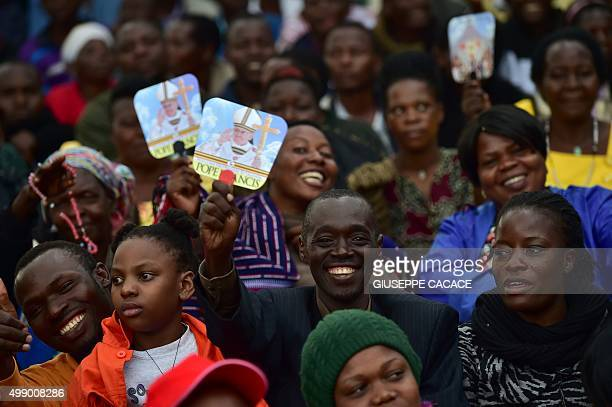 A believer holds a picture of Pope Francis as people wait for the arrival of the pope for an open mass at Namugongo Martyrs' Shrine in Namugongo...