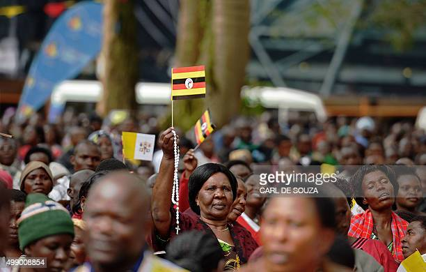 A believer holds up a Uganda flag at Namugongo Martyrs' Shrine during an open air mass held by Pope Francis on November 28 2015 Pope Francis arrived...