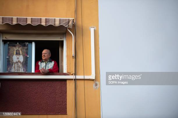 Believer seen on his balcony during a Holy Monday in downtown Malaga. The traditional Easter celebration has been cancelled in Spain. Believers live...