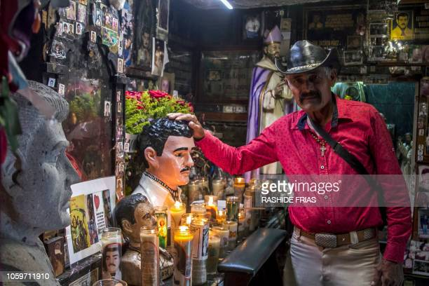 A believer tourches the bust of narcosaint Jesus Malverde at his chapel in Culiacan Sinaloa state Mexico on October 22 2018 In spite of being in New...