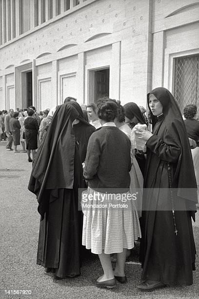 Believers and nuns standing in a queue in front of the church of Santa Maria delle Grazie in San Giovanni Rotondo
