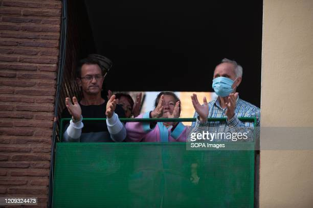 Believers applauding on their balcony as they show gratitude to doctors and nurses during a Holy Monday in downtown Malaga. The traditional Easter...
