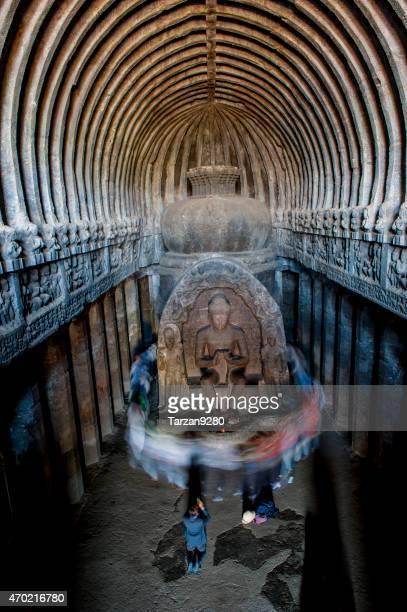 Believers circling buddha statue praying, India