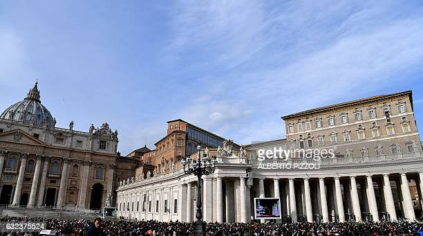 Believers gather as Pope Francis speaks from the window of the Apostolic Palace overlooking St Peter's Square during his Sunday Angelus prayer at the...