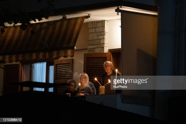 Believers in balconies in block of flats holding candles. Greek Orthodox Easter celebration during the Covid-19 national strict lockdown era in...