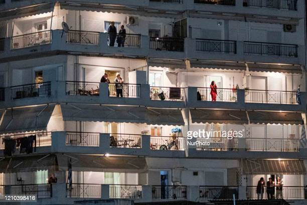 Believers in balconies in block of flats holding candles Greek Orthodox Easter celebration during the Covid19 national strict lockdown era in...