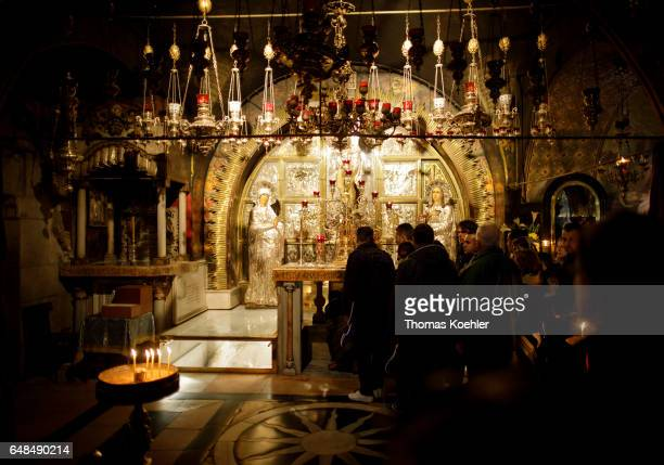 Believers in froht of an altar in the Church of the Holy Sepulchre, historic city center of Jerusalem on February 08, 2017 in Jerusalem, Israel.