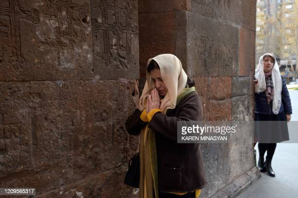 Believers keep distance as they pray in front of the Katoghike Holy Mother of God Church on Holy Thursday amid the COVID-19 coronavirus outbreak in...