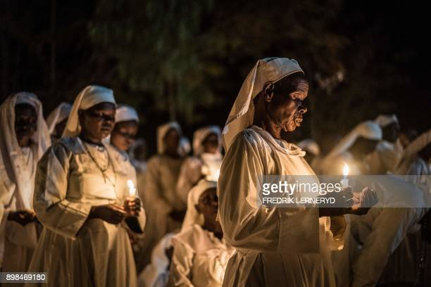 Believers of Legio Maria of African Church Mission hold candles during their overnight Christmas Mass at the church near Ugunja the western part of...