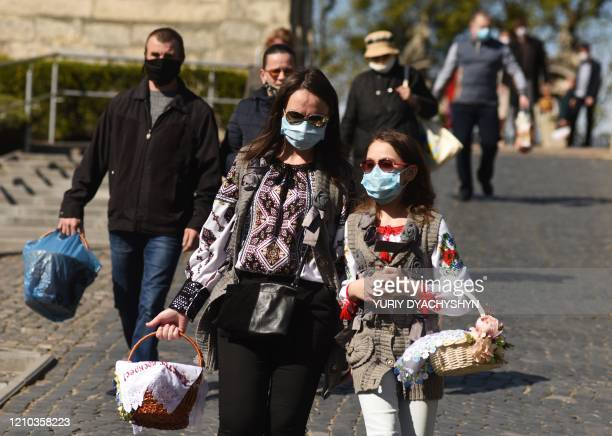 Believers of the Greek Catholic Church with face masks walk holding baskets with Easter eggs and food during the celebration of Orthodox Easter...