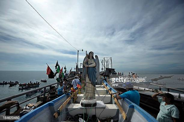 Believers place the image of Saint Raphael the Archangel before the start of a procession at the port of La Libertad 35 km south of San Salvador on...