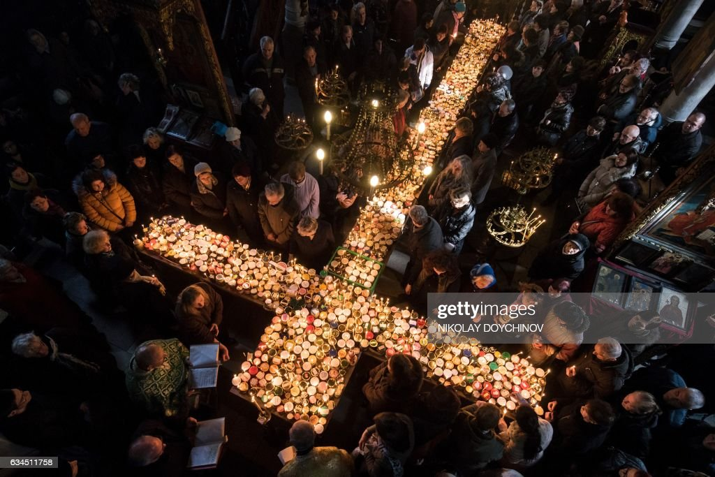 TOPSHOT - Believers pray around a cross-shaped platform covered with candles placed in jars of honey during a ceremony marking the day of Saint Haralampi, Orthodox patron saint of bee-keepers, at the Church of the Blessed Virgin in Blagoevgrad, eastern Bulgaria, on February 10, 2017. / AFP / NIKOLAY