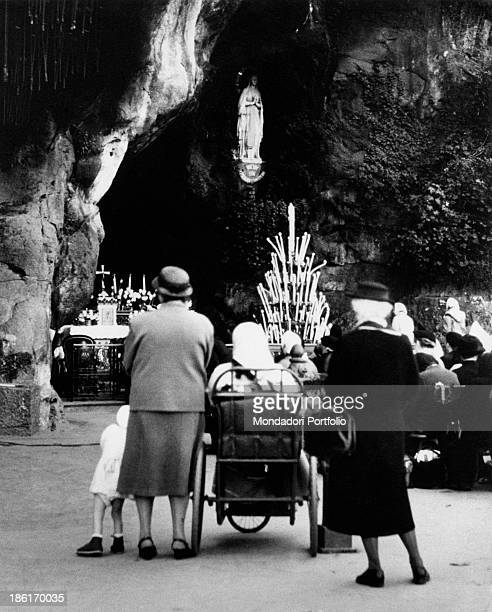 Believers praying in the Grotto of Massabielle during the centenary of the apparitions of Our Lady to Saint Bernadette Soubirous Lourdes 22nd...
