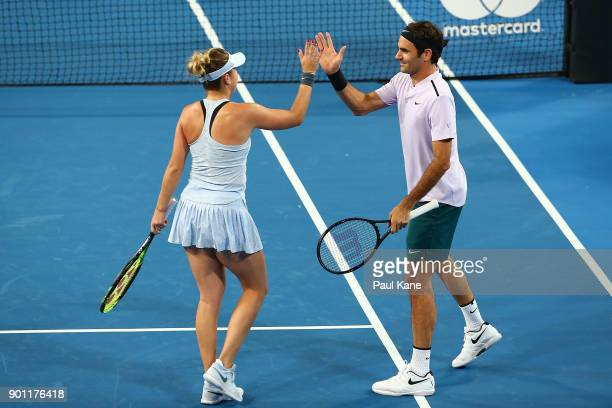 Belinda Bencic and Roger Federer of Switzerland celebrate winning a set in the mixed doubles match against CoCo Vandeweghe and Jack Sock of the...